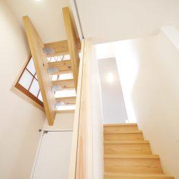 2世帯住宅・玄関土間の吹き抜け。家族をつなぐスキップフロア。木製のストリップ階段から、明かりと風が注ぎます。