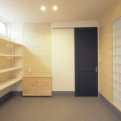 トレーニング室と自然素材と。実家裏の狭小地の家。ガラスブロックの向こうはタタミ室。家族とのつながりをそっと持たせています。