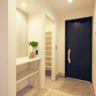 実家の敷地を分けて建てる。細長コンパクトな家。玄関はいたってシンプルに。空間をデザインしたLDKへの序章として。