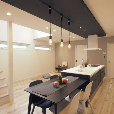 実家の敷地を分けて建てる。細長コンパクトな家。一直線のキッチンとダイニングがこの家のスマートさを強調する。
