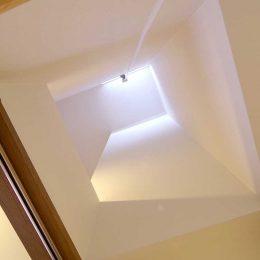グリーンスタイルのお家見学会です。階段足元。高く吹き抜ける。縦長く狭い空間をぶつかって届くかすかな光に解放感を受ける。